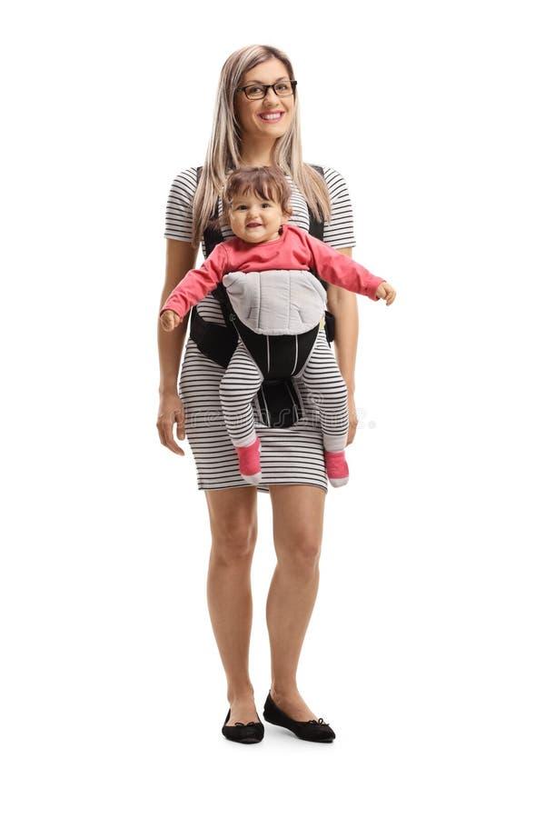 Madre feliz y un beb? en un portador imagen de archivo