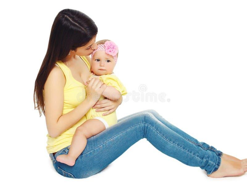 Madre giovane amorosa che bacia bambino sveglio fotografie stock libere da diritti