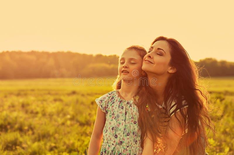 Madre godente felice che abbraccia la sua ragazza joying di rilassamento del bambino e che respira aria fresca con gli occhi chiu fotografia stock libera da diritti