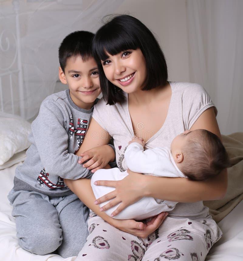 Madre hermosa con el pelo oscuro corto y ella su y pequeño bebé fotografía de archivo