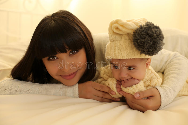 Madre hermosa con el pelo oscuro corto y su pequeño bebé lindo imagenes de archivo