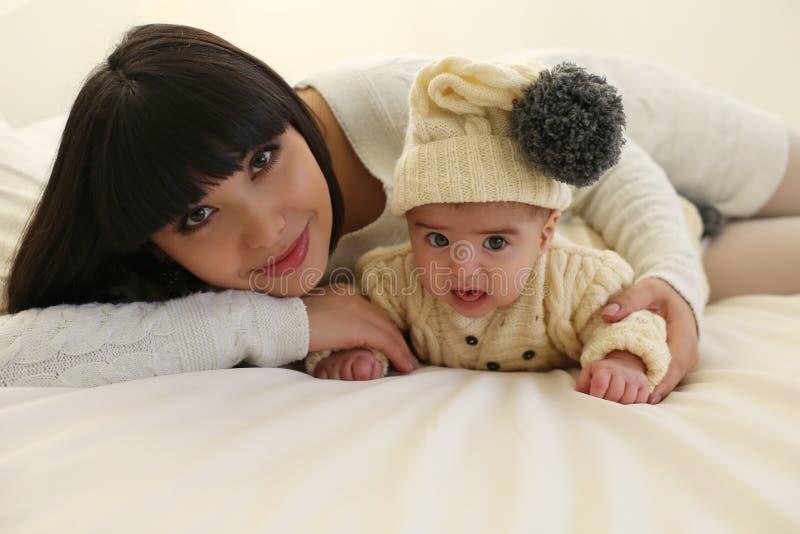 Madre hermosa con el pelo oscuro corto y su pequeño bebé lindo fotos de archivo