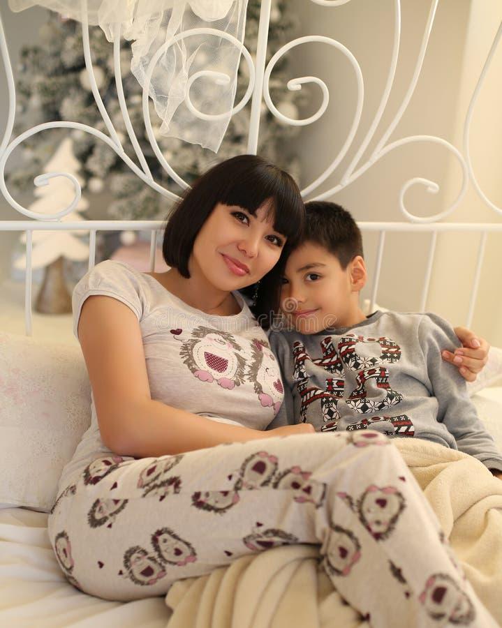 Madre hermosa con el pelo oscuro corto y su pequeño hijo imagenes de archivo