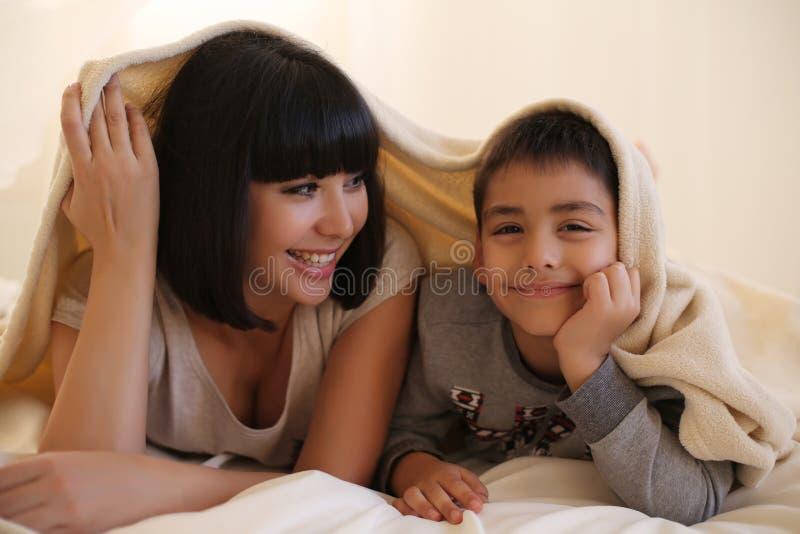 Madre hermosa con el pelo oscuro corto y su pequeño hijo foto de archivo