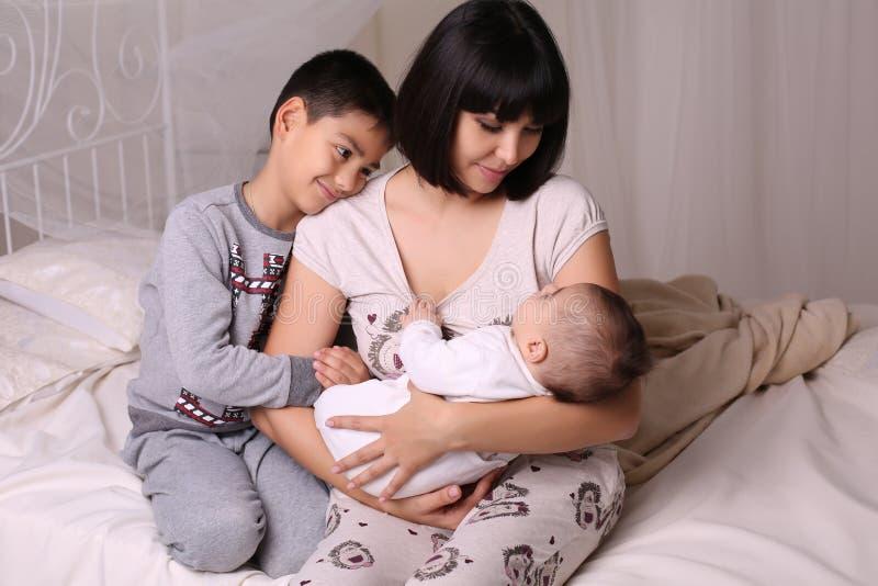 Madre hermosa con el pelo oscuro corto y sus 2 niños foto de archivo
