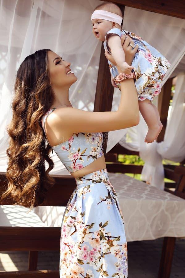Madre hermosa con el pelo oscuro largo que presenta con su pequeño bebé lindo en vestidos similares imagen de archivo