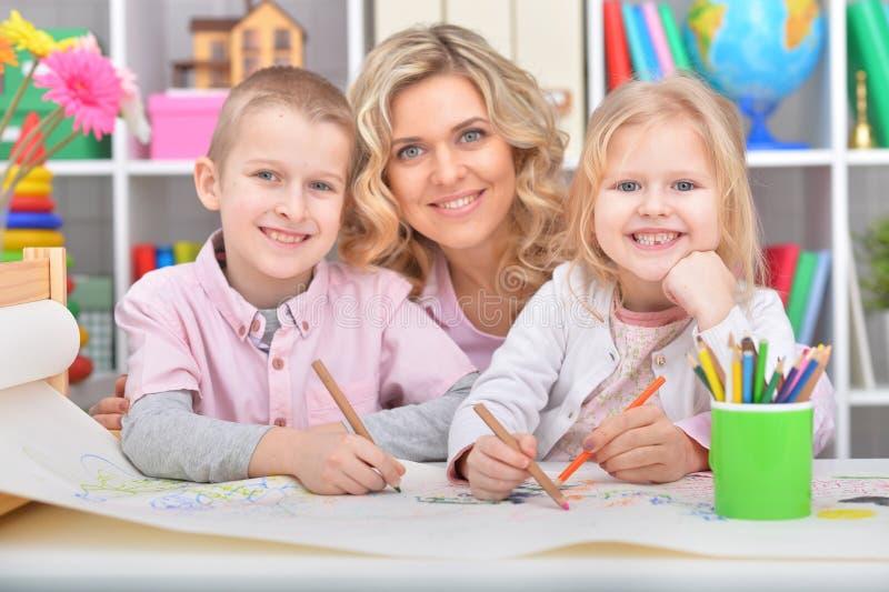 Madre hermosa con la hija que dibuja con los lápices coloridos fotos de archivo libres de regalías