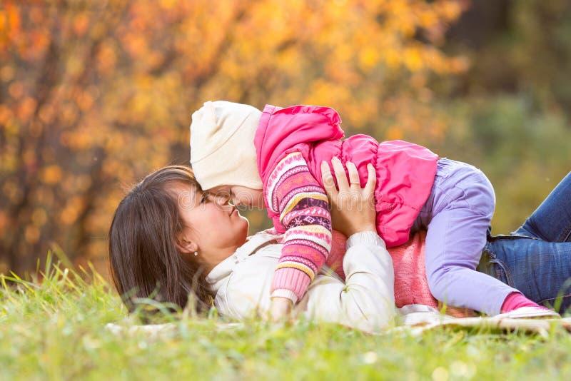Madre hermosa con la muchacha del niño al aire libre en otoño fotografía de archivo