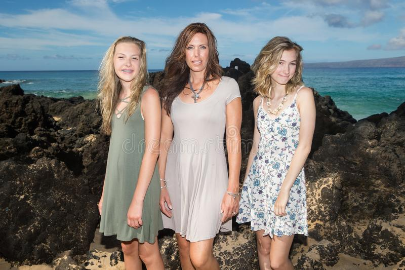 Madre hermosa con sus dos hijas en una playa imagen de archivo