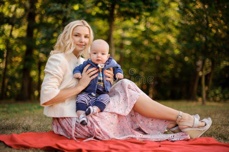 Madre hermosa con un hijo del bebé en la manta imagenes de archivo