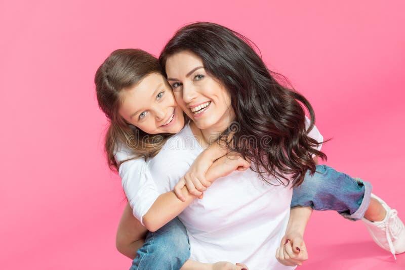 Madre hermosa e hija que abrazan y que sonríen en la cámara foto de archivo