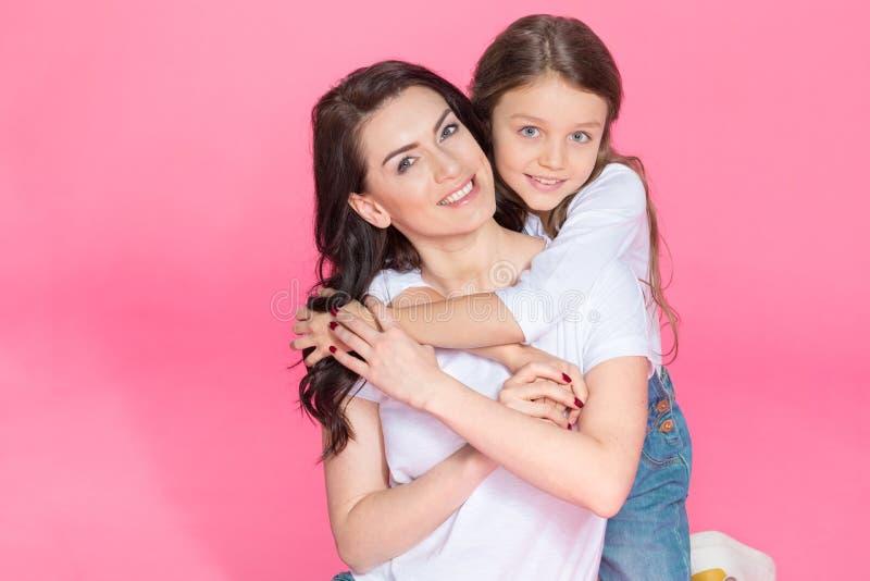 Madre hermosa e hija que se sientan junto y que abrazan en rosa imagenes de archivo