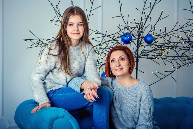 Madre hermosa e hija sonrientes felices, sentándose en el sofá con las decoraciones de la Navidad fotos de archivo libres de regalías