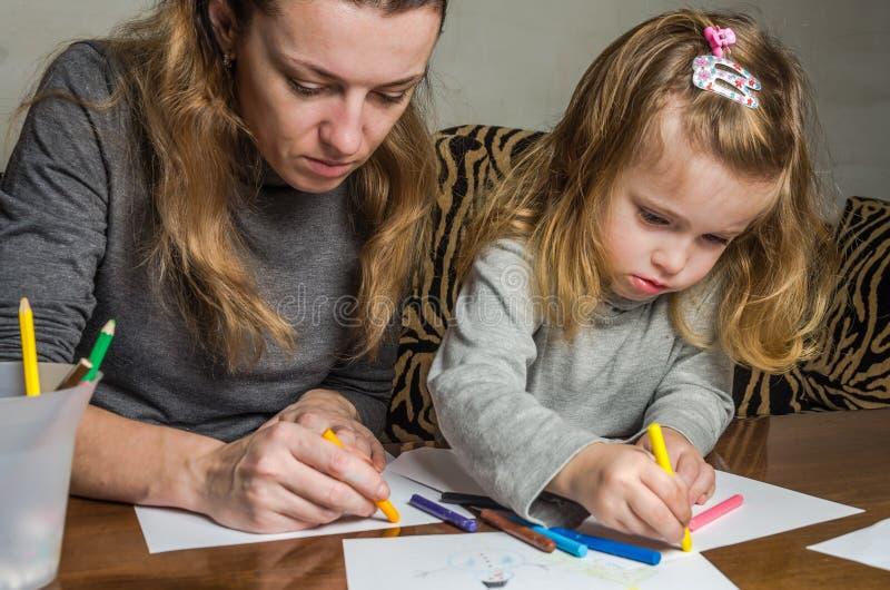 Madre hermosa joven con su drenaje de la hija con los lápices coloridos en el papel, familia feliz fotografía de archivo libre de regalías