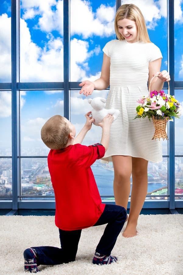 Madre hermosa joven con su hijo y un ramo de flores El niño da a madre un pequeño oso de peluche, sorpresa Conce de la primavera foto de archivo