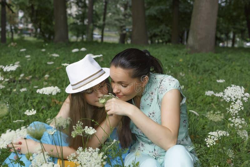 Madre hermosa joven con una sonrisa feliz en su cara con su hija adolescente que descansa en el parque en las flores el oler de l fotos de archivo