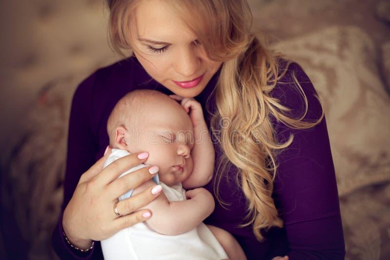 Madre hermosa joven que celebra al bebé recién nacido durmiente en las manos adentro imagen de archivo libre de regalías