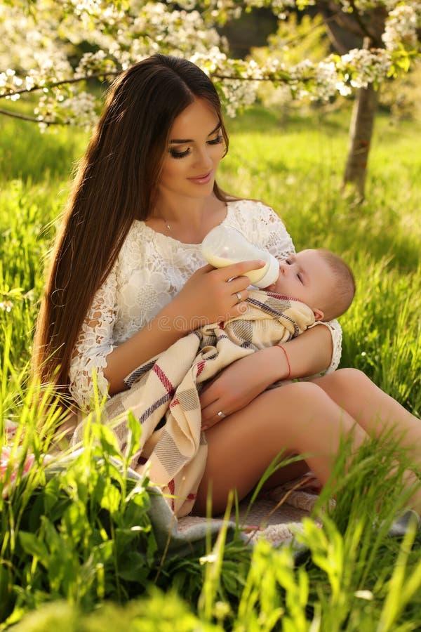 Madre hermosa que presenta con su pequeño bebé lindo en jardín del flor fotos de archivo libres de regalías