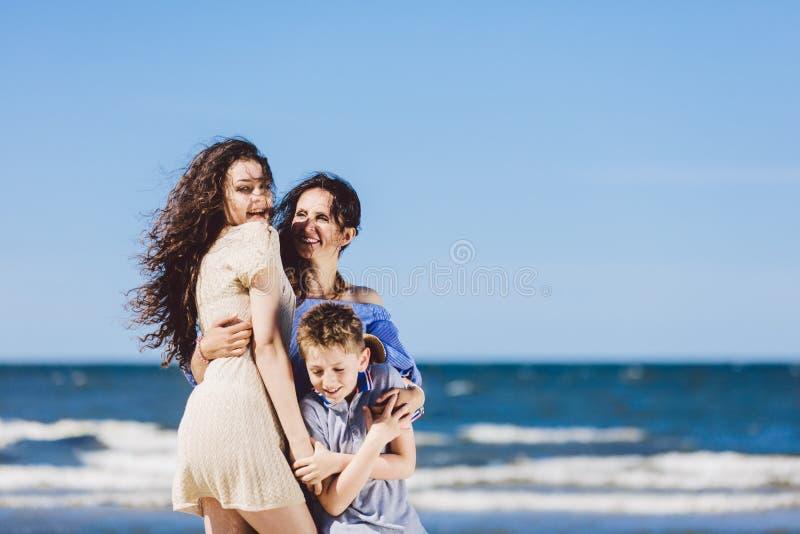 Madre, hija e hijo abrazando en la playa imagen de archivo