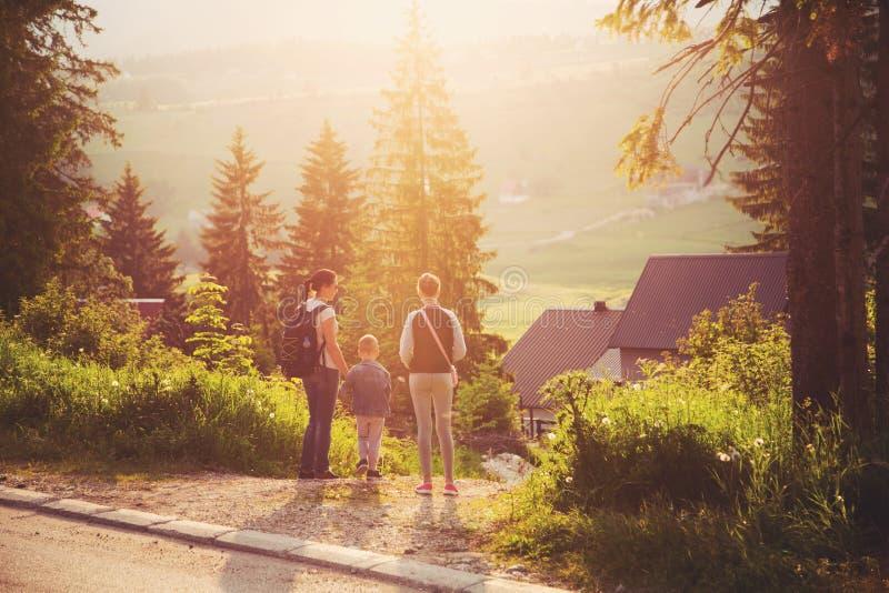 Madre, hijo e hija caminando en bosque fotos de archivo