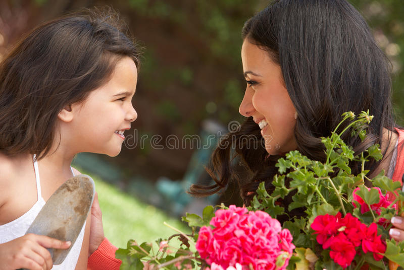 Madre hispánica e hija que trabajan en el jardín que pone en orden los potes fotografía de archivo libre de regalías