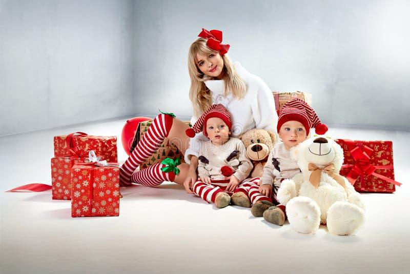 Madre incantante che posa con i suoi figli gemellati immagine stock libera da diritti