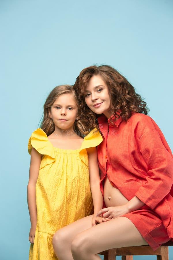 Madre incinta con la figlia teenager Ritratto dello studio della famiglia sopra fondo blu immagine stock