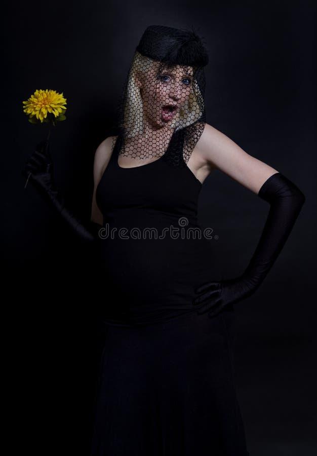 Madre incinta dei giovani con il fiore giallo immagini stock libere da diritti