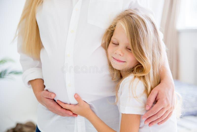 Madre incinta sorridente felice che abbraccia con sua figlia a casa fotografia stock libera da diritti