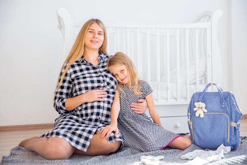 Madre incinta sorridente felice che abbraccia con sua figlia a casa fotografie stock libere da diritti
