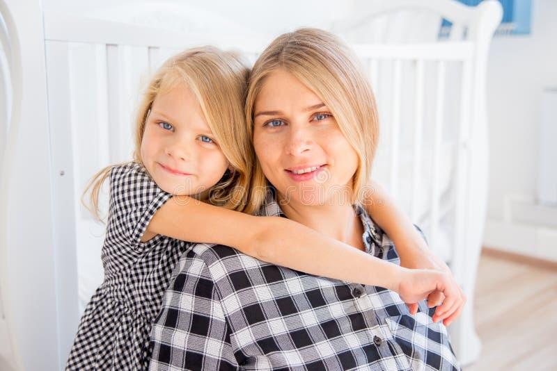 Madre incinta sorridente felice che abbraccia con sua figlia a casa fotografia stock