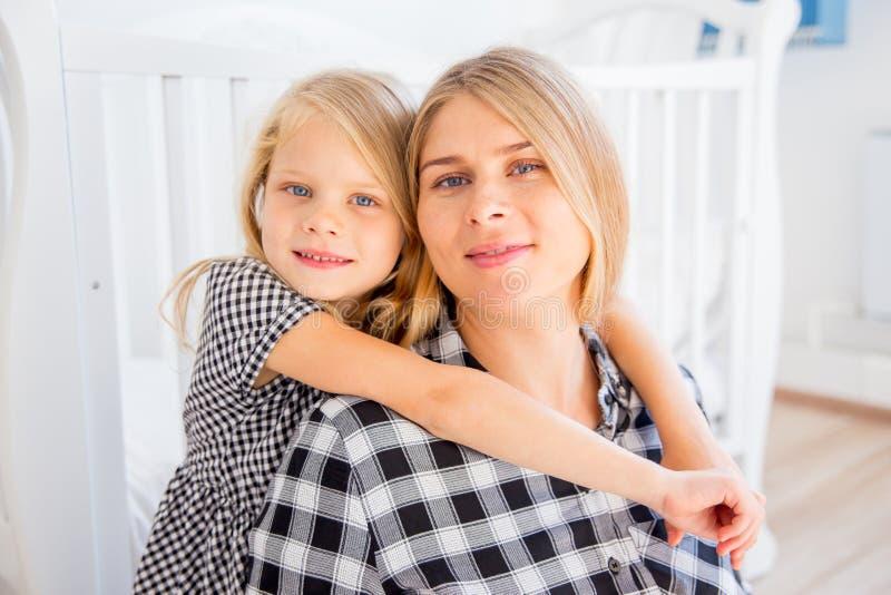 Madre incinta sorridente felice che abbraccia con sua figlia a casa immagini stock