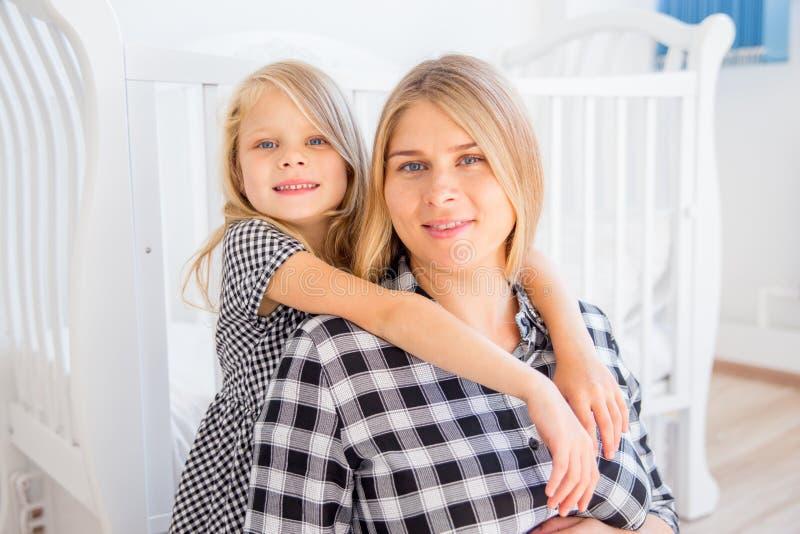 Madre incinta sorridente felice che abbraccia con sua figlia a casa immagine stock