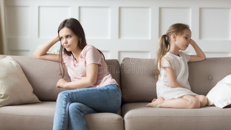 Madre insoddisfatta e piccola figlia che si siedono sullo strato che guarda da parte fotografie stock