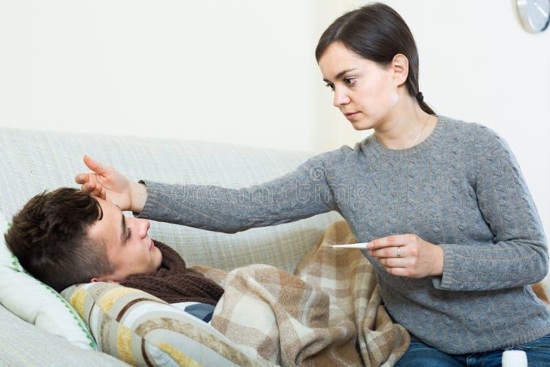 Madre interessata che dà miscela al figlio adolescente con la tosse fotografia stock libera da diritti