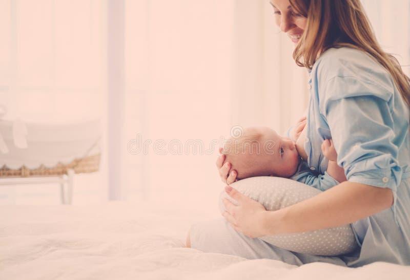Madre invecchiata media felice che allatta il suo bambino immagini stock libere da diritti