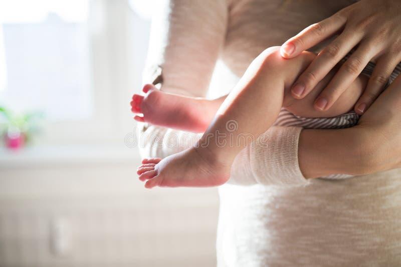 Madre irreconocible con el hijo, las piernas y las manos recién nacidos del bebé fotografía de archivo