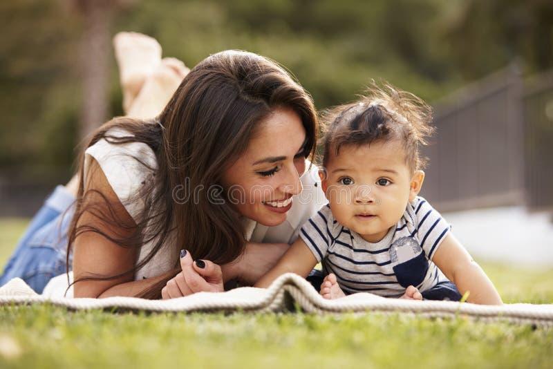 Madre ispana millenaria che si trova su una coperta nel parco con il suo bambino che sorride, fine su fotografia stock
