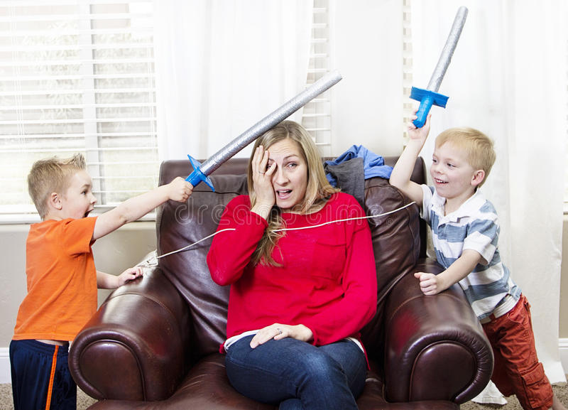 Madre joven abrumada por sus niños imagen de archivo