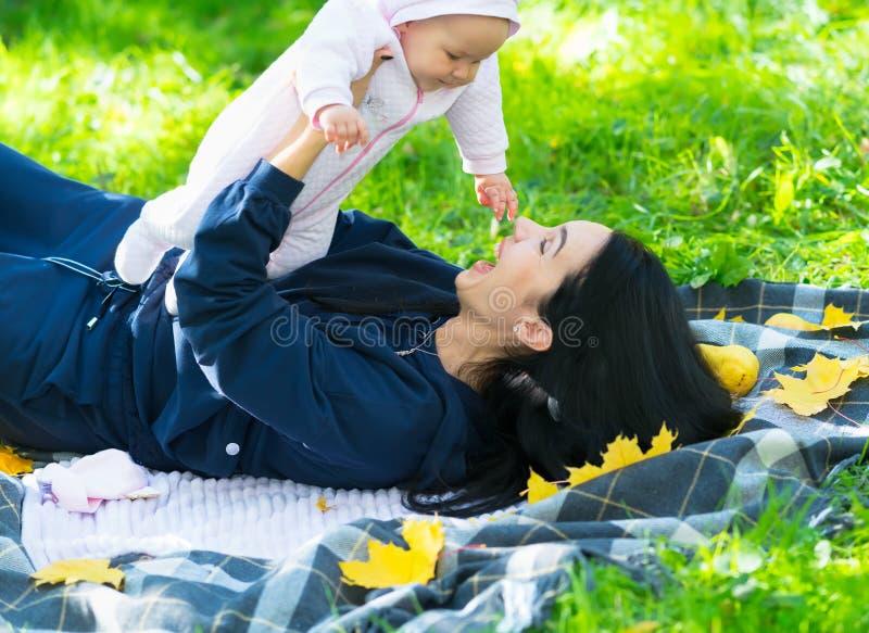 Madre joven alegre que juega con una pequeña hija fotografía de archivo