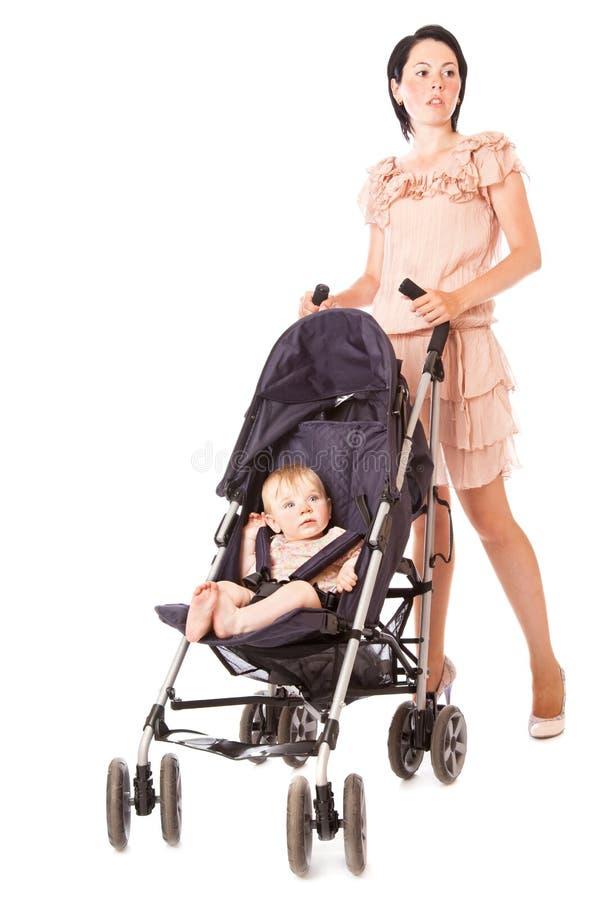 Madre joven con el bebé en cochecito de niño imagen de archivo