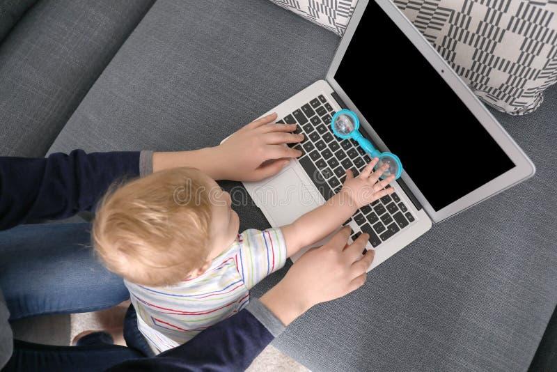 Madre joven con el bebé que usa el ordenador portátil en casa, visión superior imágenes de archivo libres de regalías