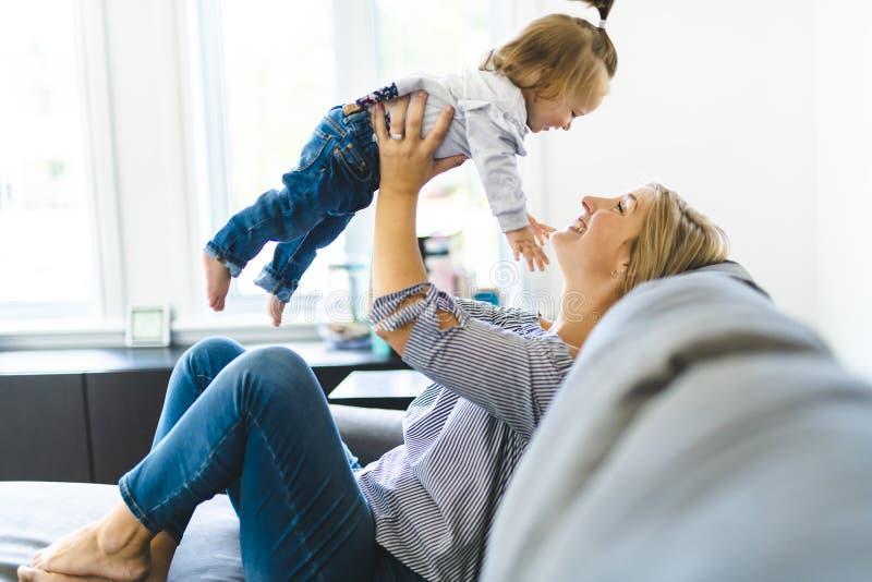 Madre joven con la hija del bebé en el sofá en casa imagen de archivo libre de regalías
