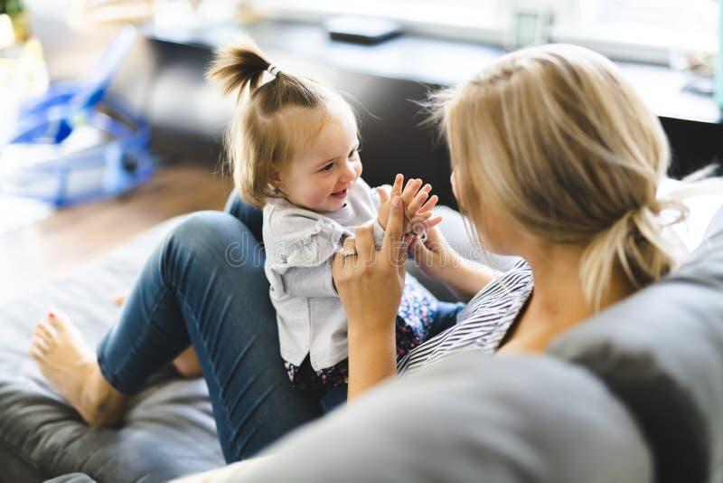 Madre joven con la hija del bebé en el sofá en casa fotos de archivo libres de regalías