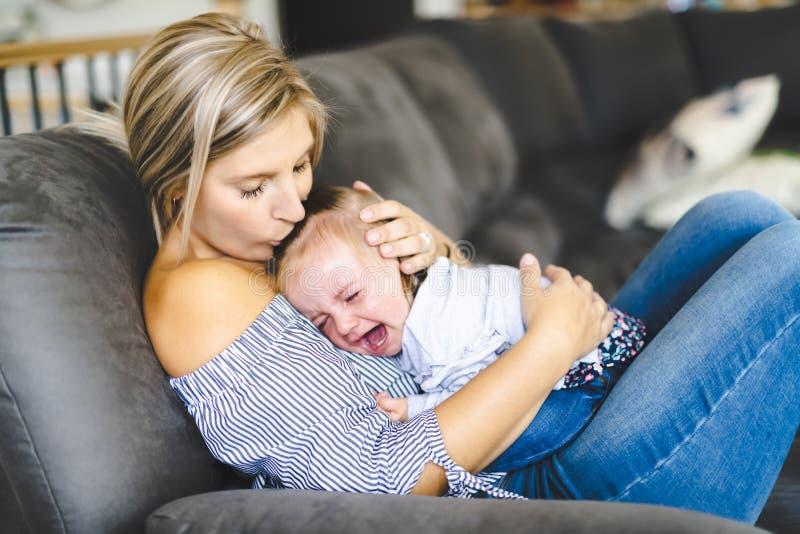 Madre joven con la hija del bebé en el sofá en casa, el griterío del bebé foto de archivo libre de regalías