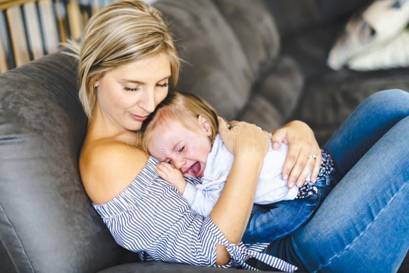 Madre joven con la hija del bebé en el sofá en casa, el griterío del bebé foto de archivo