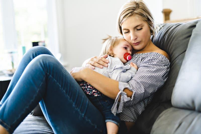Madre joven con la hija del bebé en el sofá en casa, el griterío del bebé fotografía de archivo libre de regalías