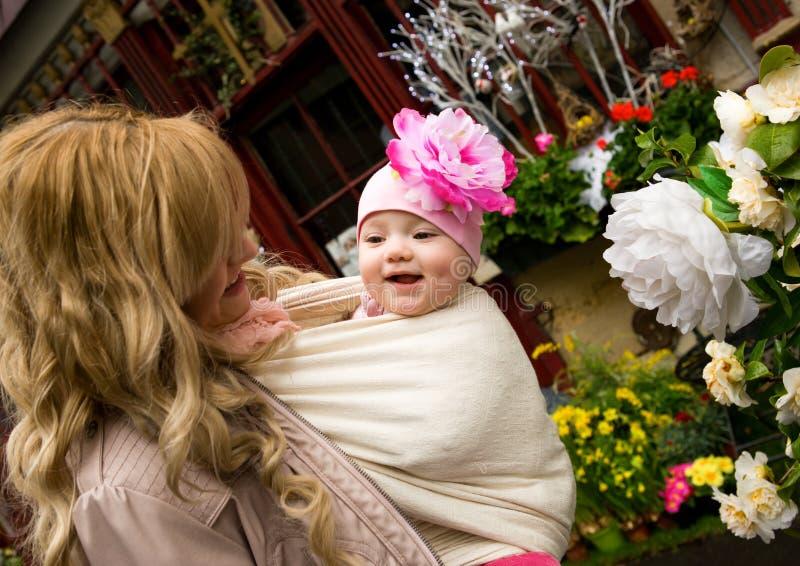 Madre joven con la hija del bebé en un jardín imágenes de archivo libres de regalías