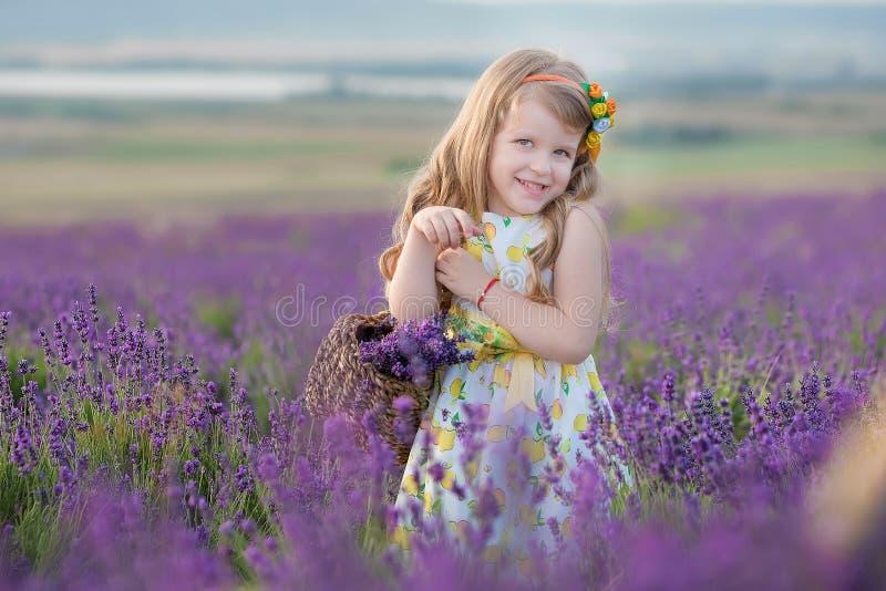 Madre joven con la hija joven que sonríe en el campo de la lavanda Hija que se sienta en las manos de la madre Muchacha en colori imagen de archivo