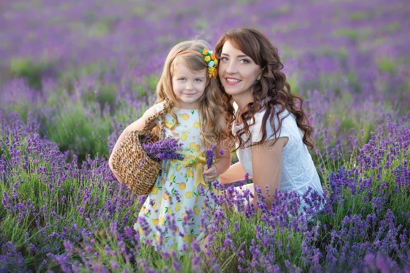 Madre joven con la hija joven que sonríe en el campo de la lavanda Hija que se sienta en las manos de la madre Muchacha en colori foto de archivo